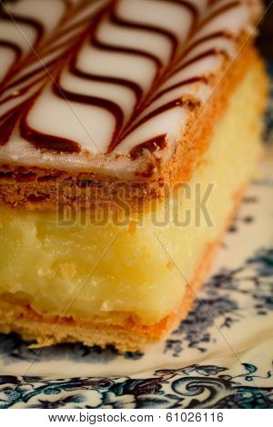 Close up of a millefeuille, french pastry with custard on wooden table