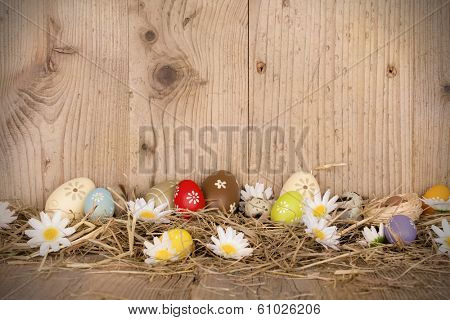 Easter colored eggs in nest. Wooden surface around