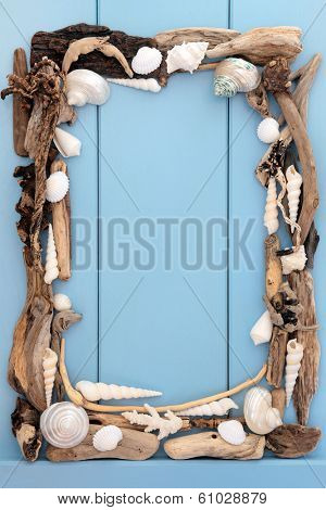 Sea shell and driftwood abstract border over wooden blue background.