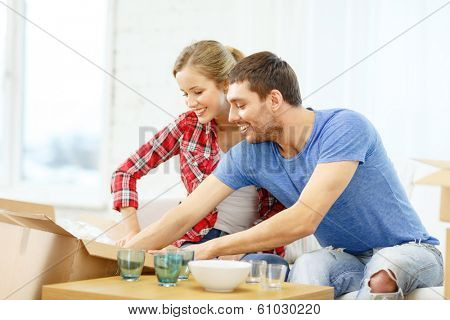 repair, building and home concept - smiling couple unpacking kitchenwear