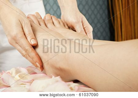 woman foot receiving gentle massage on bed with rose petals in spa