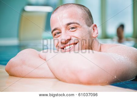 Young attractive male posing with a smile in a swimming pool