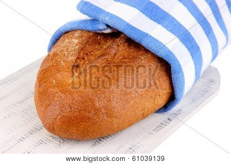 Rye bread in napkin on wooden stand close up