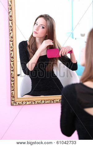Young beautiful woman making hairstyle near mirror