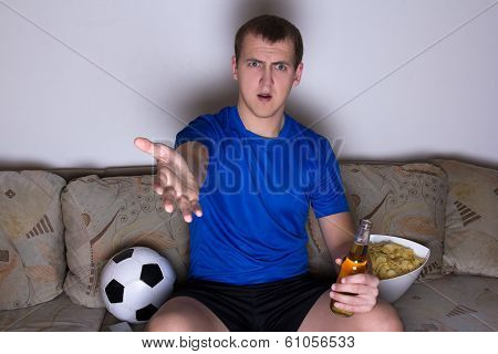 Shocked Emotional Supporter In Uniform Sitting On The Sofa And Watching Soccer With Beer And Chips
