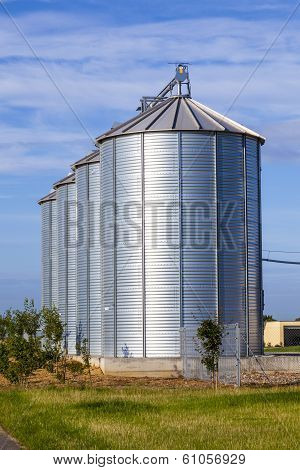 four silver silos in rural landscape in morning light