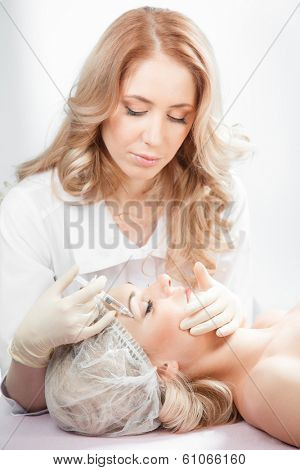Young woman receiving a botox injection in her face, close up