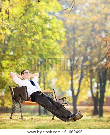 Businessman relaxing in park, seated on a wooden bench shot with tilt and shift lens
