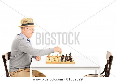 Senile old man playing a game of chess alone isolated on white background