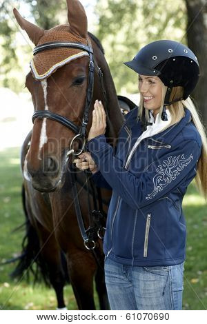Female rider in equestrian helmet caressing horse, smiling.
