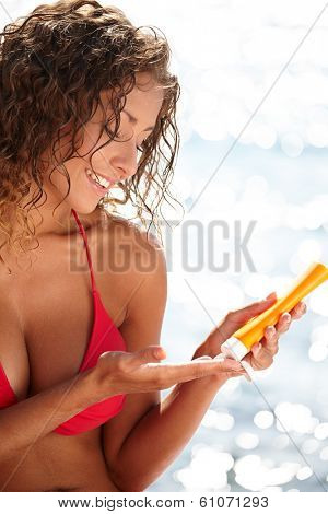 beautiful young woman in bikini smear protective cream on the skin on the beach under the sun