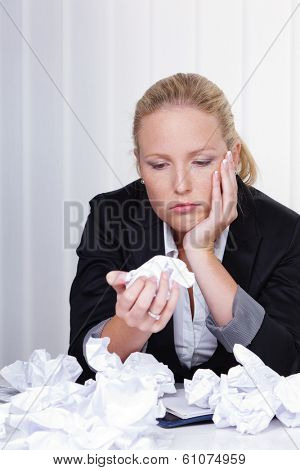 a woman in the office with crumpled paper. anger, stress and frustration in the workplace