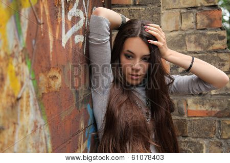 beautiful young girl against brick wall