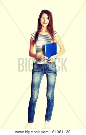 Front view of a full lenght young happy female caucasian student holding a notebook, on white.