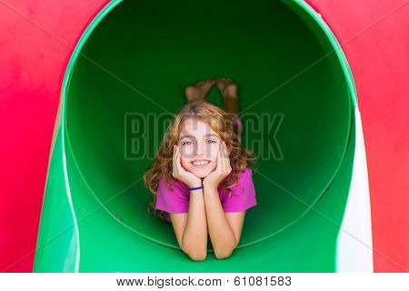 kid girl smiling in the park playground relaxed with hands in face