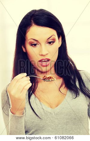 Young beautiful caucasian woman shocked while eating a cake -spoon bending - too much callories concept