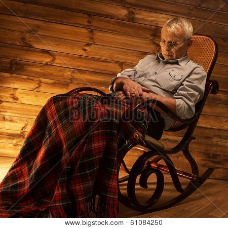 Senior man fell asleep on rocking chair in homely wooden interior