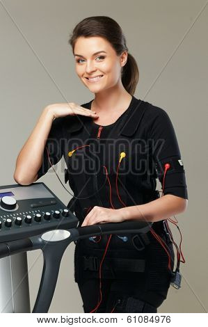 Young woman in training costume near Electro Muscular Stimulation EMS machine