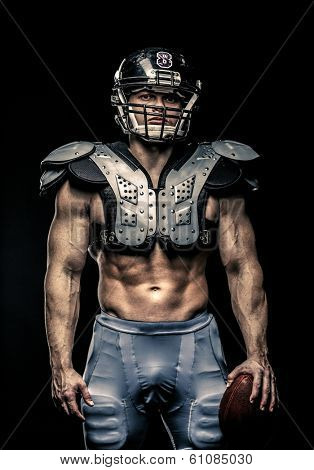 American football player with ball wearing helmet and protective shields