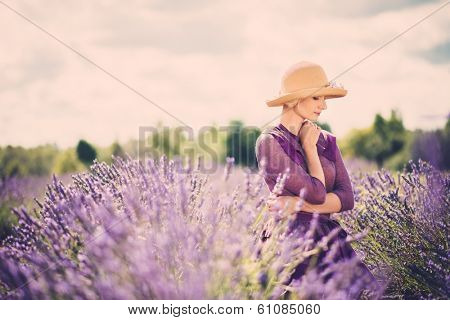 Woman in purple dress and hat in lavender field