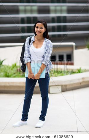pretty college student outside school building holding book