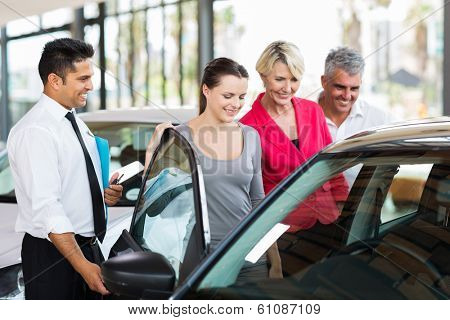 handsome car salesman showing a new car to a family