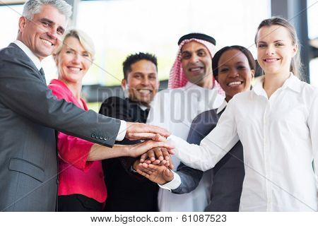 close up of multiracial business team putting their hands together, focus on hands