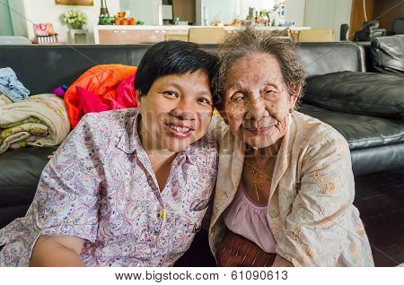 Family Portrait of an Asian elder mother and daughter hold together in home scenery