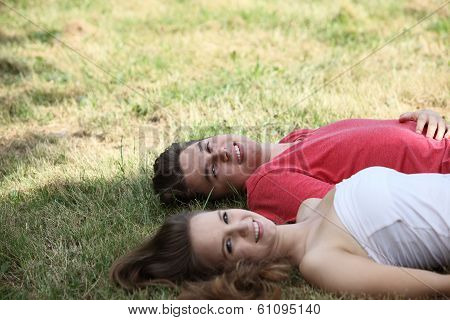 Smiling Happy Teenage Couple Relaxing On Grass