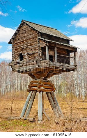 Wooden House On Poles In The Field