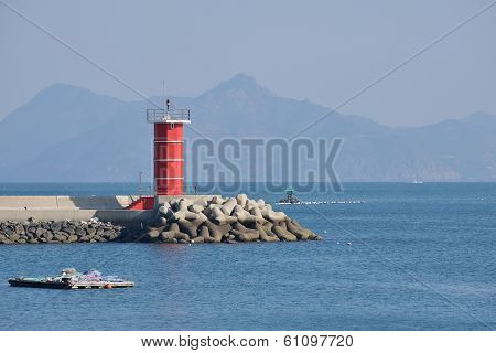 Red Lighthouse On The End Of Breakwater With Tetrapod