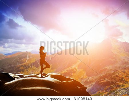 Woman standing in tree yoga position, meditating on rock in mountains at sunset. Zen, meditation, peace