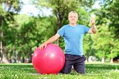 Healthy man giving thumb up seated on an exercise mat in a park