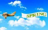 Vintage wooden toy plane flying in blue sky pulling a banner to bring in spring