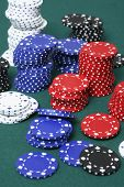 Gambling chips in different colors on green background