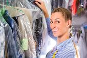 stock photo of laundry  - Female cleaner in laundry shop or textile dry - JPG