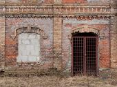stock photo of corbel  - Wall of an old deserted brick building with architectural details - JPG