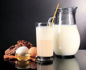 Eggnog with milk and eggs on grey background
