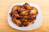 stock photo of mesquite  - Fried chicken wings with mesquite sauce on a white plate - JPG