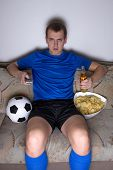 Bored Man In Football Uniform Sitting In Living Room And Watching Tv With Chips And Beer
