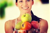 stock photo of fruit bowl  - Young fit woman with bowl of exotic fruits - JPG