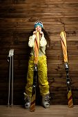 stock photo of ski boots  - Happy woman with skis and ski boots near wooden wall  - JPG