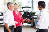 picture of showrooms  - senior couple receiving car key after buying a new car - JPG