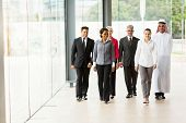 group of professional businesspeople walking in office building
