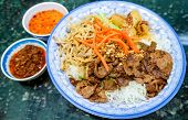 picture of rice noodles  - Traditional bowl of Vietnamese bun vermicelli rice stick noodle salad with charbroiled meat shredded pork deep fried spring rolls and pickled carrots served with mint leaves peanuts and fish sauce - JPG