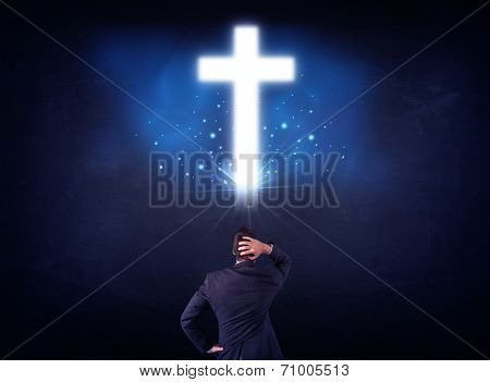 Young businessman standing and looking at a glowing cross above his head