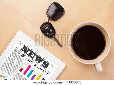 Workplace with tablet pc showing latest news and a cup of coffee on a wooden work table close-up