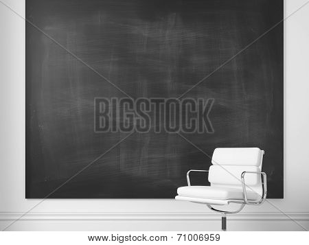 White office chair and blank chalkboard on a wall