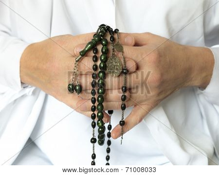 Hands in prayer with beads