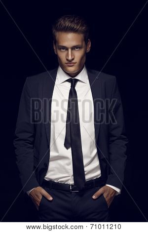 Cool Businessman Standing On Dark Background